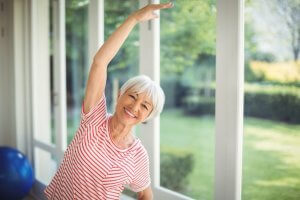 Portrait of happy senior woman performing stretching exercise
